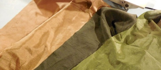 Sample colors swatches in green and gold, microsuede and man-made silk.